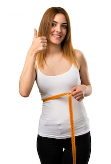 Slim woman with tape measure with thumb up