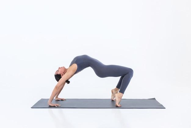 Slim woman yogi practices yoga on mat standing in bridge pose doing stretching