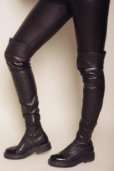黒革パンツとスタイリッシュなハイブーツのスリムな女性の足。