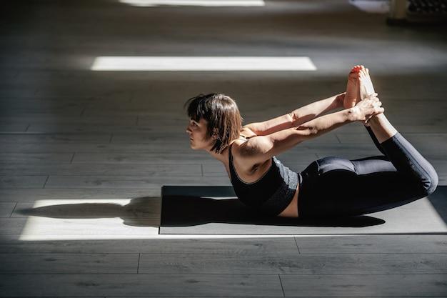 Стройная женщина йоги с короткими каштановыми волосами в позе йоги лук. интерьер студии йоги.