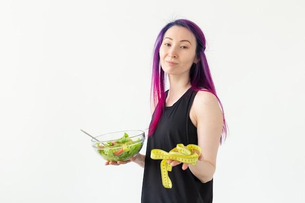 色付きの髪のスリムな若いアジアの女の子は、測定テープをぶら下げ、白い背景でポーズをとって彼女の手で軽い野菜サラダを持って測定されます。健康的な食事の概念。コピースペース