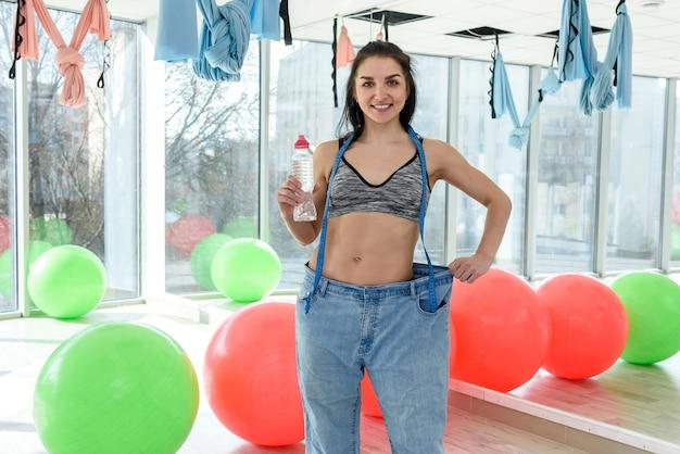 물 한 병을 가진 슬림 젊은 매력적인 여자, 피트니스 클럽이나 체육관에서 체중 감량의 결과를 보여줍니다. 건강한 생활