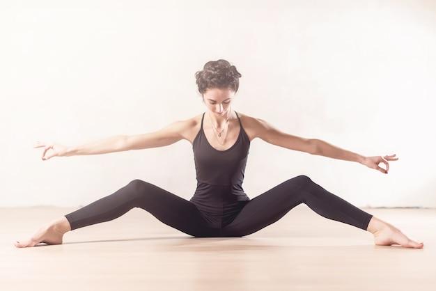 スリムな若いバレエダンサーが、屋内で足を大きく広げて座ってストレッチ運動をしています。