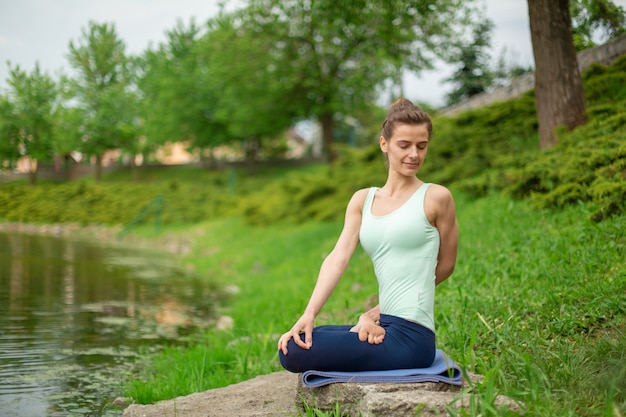 Slim young brunette yogi performs no complicated yoga exercises on the green grass in summer against the background of nature