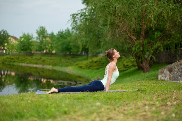 Slim young brunette yogi performs yoga exercises on the green grass