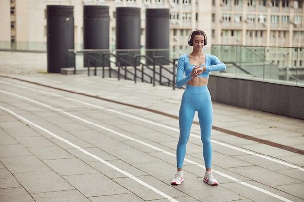 슬림 한 젊은 백인 아가씨는 도시 장소에서 야외 스포츠를하고있다