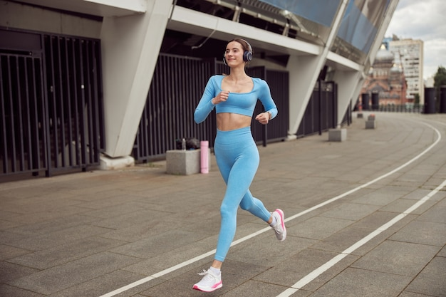 Стройная молодая кавказская дама занимается спортом на открытом воздухе в городском месте