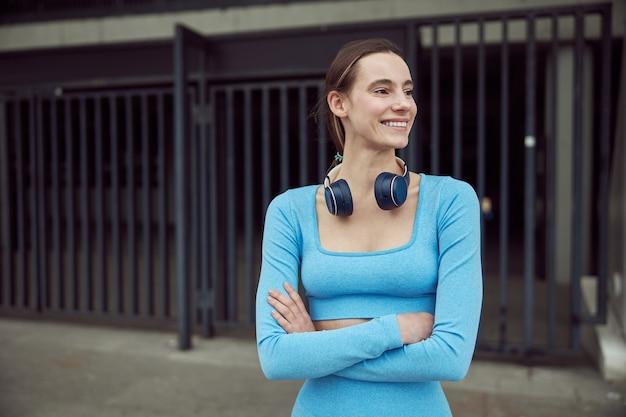 スリムな若い白人女性は都会の場所で屋外でスポーツをしています