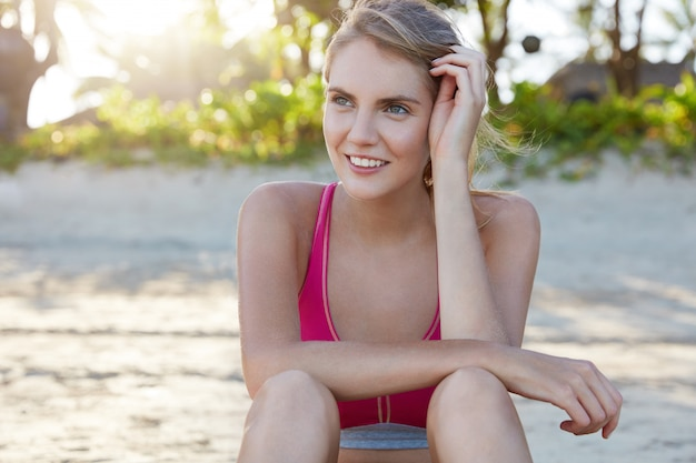 スポーツウェアのスリムな若い陽気な女性、ヨガのトレーニング運動の後に休憩、夏の時間に彼女の体の形を改善し、早朝に日の出を楽しんでいます。体調の良い女性はスポーツが好き