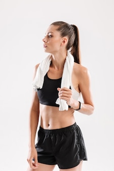Slim young fitness woman with towel on her neck standing