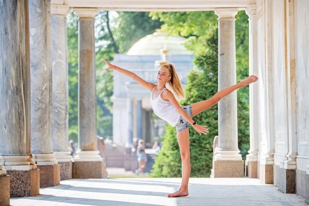 공원의 고풍스러운 건축물을 배경으로 포즈를 취한 날씬한 젊은 체조 선수