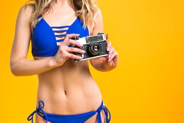 Slim young woman in bikini holding camera
