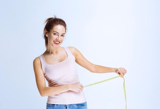 スリムな若い女性がテープで腰のサイズをチェック