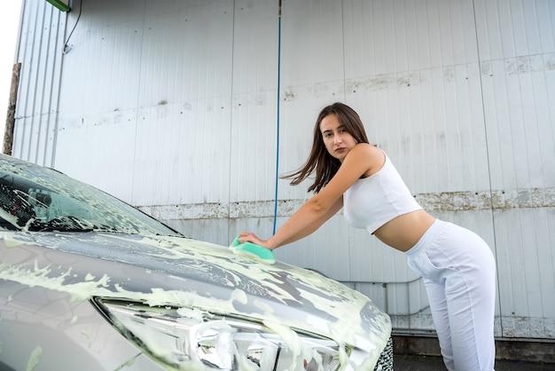 날씬한 젊은 여성이 고압 거품과 세차 스폰지를 사용하여 차를 청소합니다.