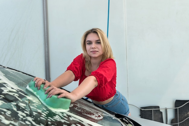 Slim young woman cleaning her car by using a high pressurized foam and car wash sponge.