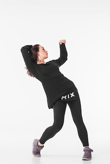 Slim young woman dancing hip hop against white background