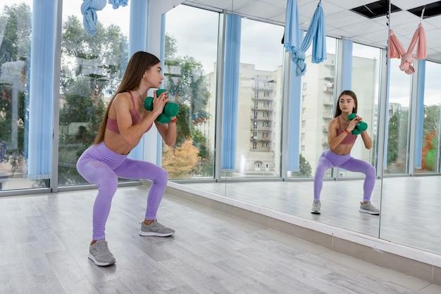 피트 니스 스포츠 체육관에서 건강 라이프 스타일에 대 한 긴장 운동을 하 고 슬림 젊은 여자.