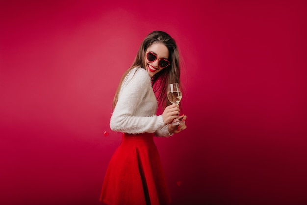 Slim young woman drinking champagne and laughing