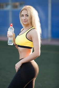 Slim young woman drinking water after training