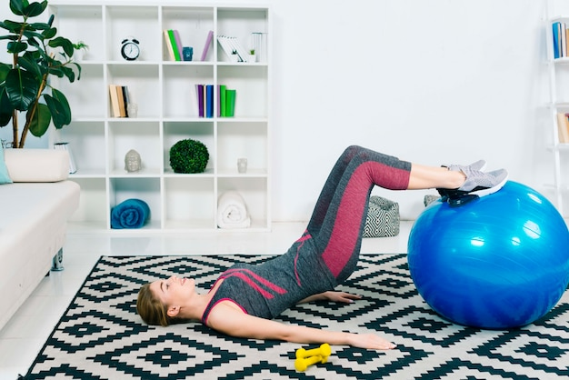 Slim young woman exercising with blue pilates ball on carpet at home