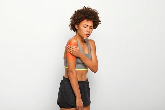スリムな若い女性は、肩の痛み、動揺した表情、スリムな体型、アクティブな服を着ています