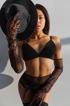 섹시 한 란제리에 슬림 젊은 여성이 검은 모자를 보유