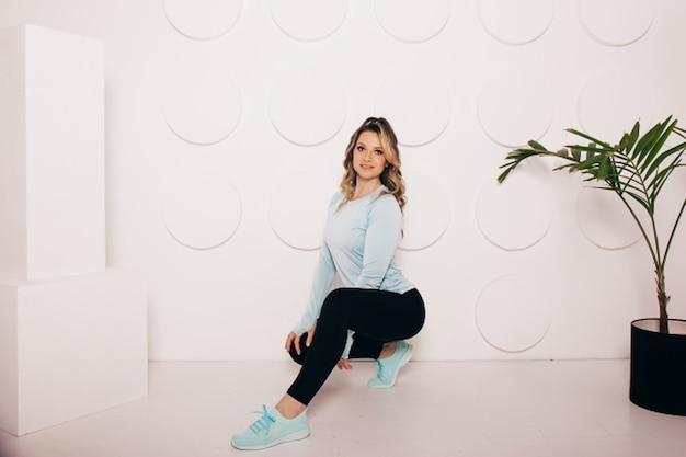 Стройная молодая женщина в спортивной одежде, счастливая, радостная. счастливая молодая женщина в спортивной одежде улыбается. мышечная фитнес-модель на белом фоне, глядя на пространство для копирования.