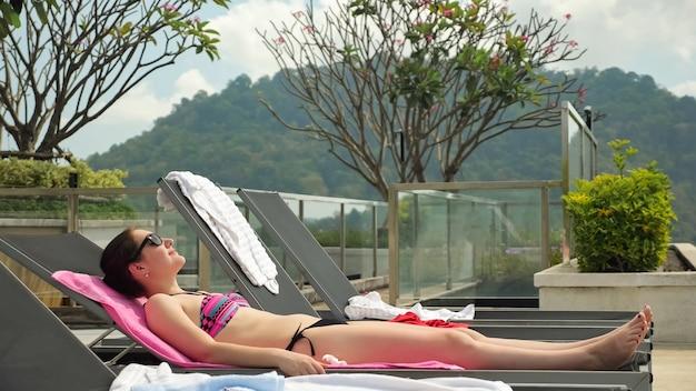 サングラスとビキニのスリムな若い女性は、森のある丘のシルエットに対してホテルのプールのそばの黒いラウンジャーで日光浴をします