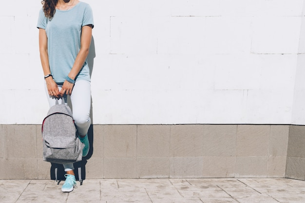 Slim young woman in jeans and t-shirt standing against a white wall with a backpack in hands