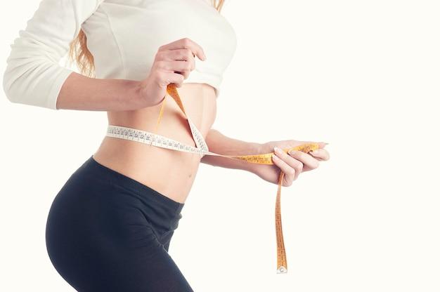줄자로 그녀의 얇은 허리를 측정하는 날씬한 젊은 여성