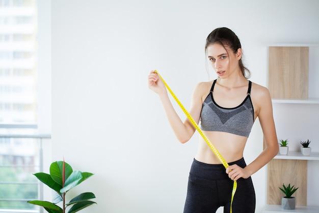 Стройная молодая женщина, измеряющая ее талию с помощью рулетки.