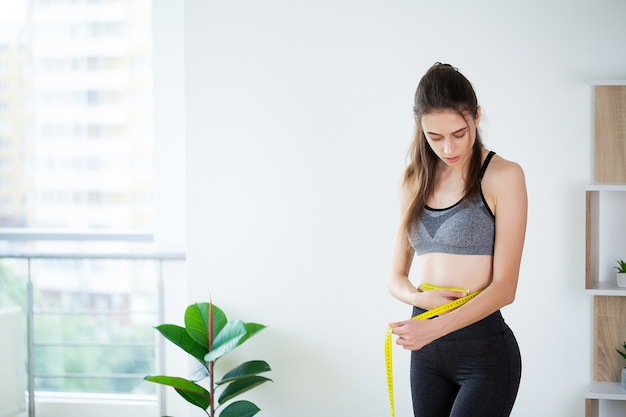 Slim young woman measuring her waist with a tape measure.