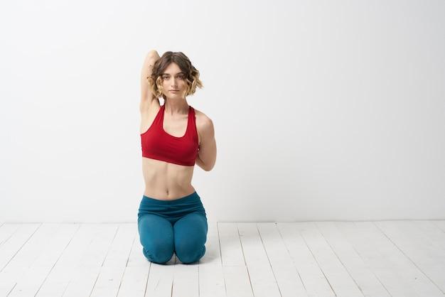 Стройная молодая женщина занимается йогой и упражнениями дома в студии