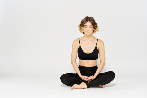 Slim young woman practices yoga and exercises at home in the studio