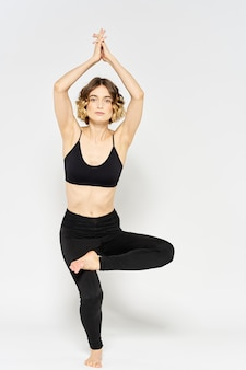 Slim young woman practices yoga and exercises at home