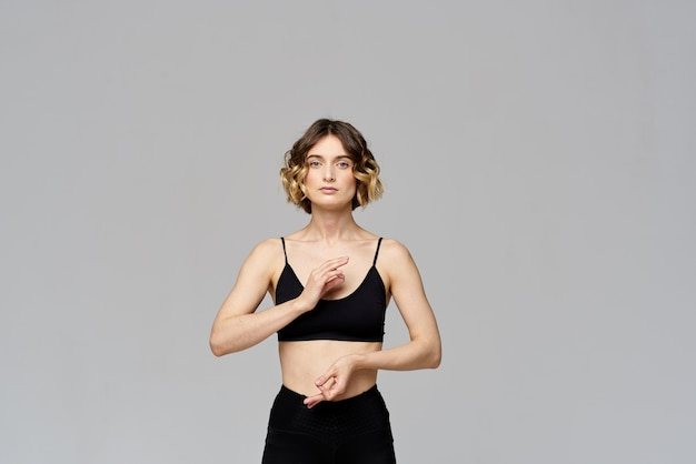 Slim young woman practices yoga and exercises