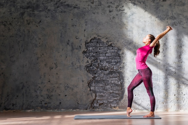 Slim young woman practicing stretching exercise against weathered wall