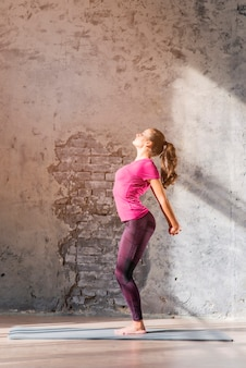 Slim young woman practicing stretching exercise standing against weathered wall