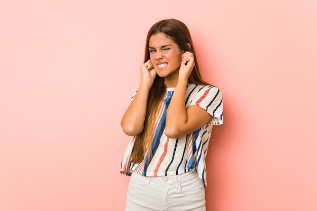Молодая женщина slim, охватывающих уши руками.