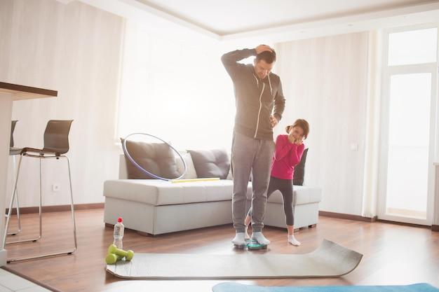 Похудение. отец и дочь взвешиваются на домашних весах. веселые и радостные моменты веселья в семье. концепция диеты, правильного питания и здорового образа жизни