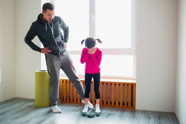 Похудение. отец и дочь взвешиваются в домашних весах. веселые и радостные моменты веселятся в семье. диета, правильное питание и концепция здорового образа жизни.