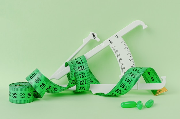 Slimming treatment concept. measuring tape, supplement and caliper