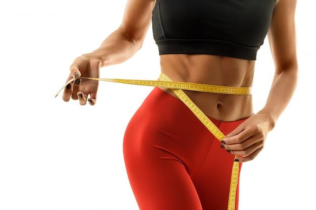 Похудение женщины в спортивной одежде с желтой мерой