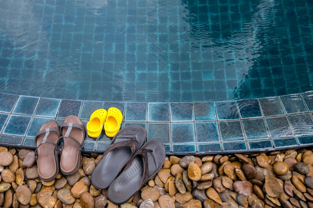 Slippers on edge of swimming pool