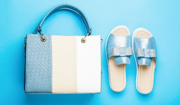青い背景のスリッパ。夏用のスリッパ。レディースバッグとスタイリッシュな青い靴