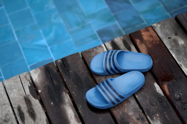 スリッパやビーチプール夏休み休暇の概念のための木製のプールサイドの靴