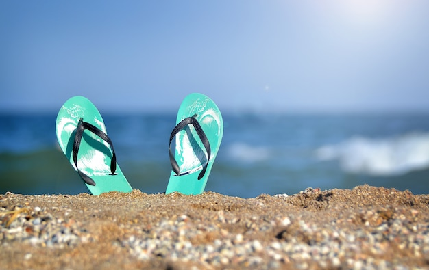 Slippers on the sand to the sea. vacation. sandals