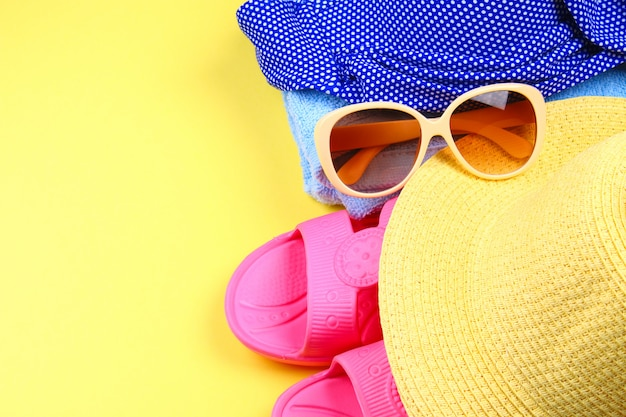 Slippers, swimsuit bikini, towel, hat and sunglasses on a pastel yellow background.