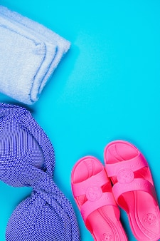 Slippers, swimsuit, towel on blue pastel background. rest, travel. top view. copy space. flat lay.