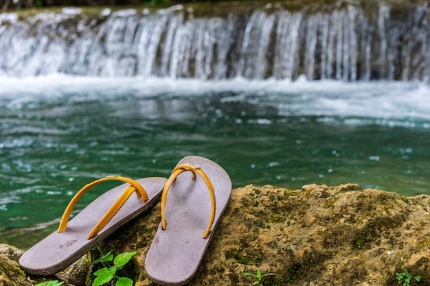 Slippers were placed on the rock in the waterfall